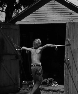 Boy hanging on rake walking to shed