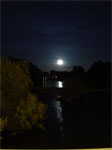 99% of full moon over river