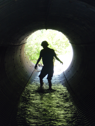 Silhouette of boy in giant runoff pipe with water